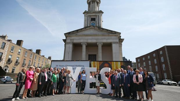 A cross party group of TDs and Senators take part in the Together for Yes billboard launch in Dublin (Niall Carson/PA)