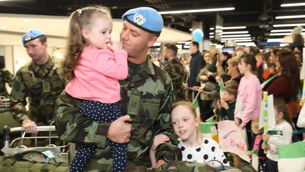 Sergeant Graham Clarkin is greeted by daughters Lauren (two) and Sophie (eight) at Dublin airport (Niall Carson/PA)