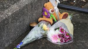 Floral tributes left outside a complex in Poddle Park, Kimmage, Dublin, where a three-year-old boy was found dead with stab wounds