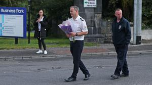 Members of the fire service carry flowers to the scene in Castlerea (Niall Carson/PA)