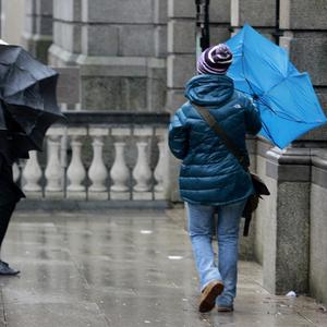 Pedestrians in Dublin's city centre struggle with their umbrellas as storms sweep across the country