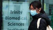 A woman wearing a face mask walks past the Trinity Biomedical Sciences Institute which forms part of Trinity College Dublin's city centre campus (Brian Lawless/PA)