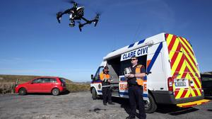 Members of the Civil Defence pilot a drone near to Annagh Head, Co Mayo