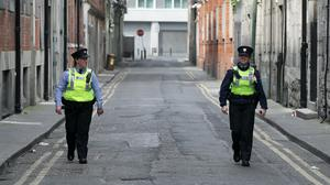 Members of An Garda maintain social distancing in Dublin's city centre as they patrol (PA)