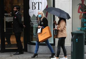 A woman carrying shopping bags leaves Brown Thomas on Grafton Street (Brian Lawless/PA)