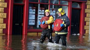 Members of the fire service work as flooding continues in Bandon, Co Cork, following Storm Frank