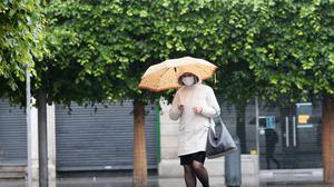 A woman wearing a protective face mask shelters from the rain on Dublin's O'Connell street.