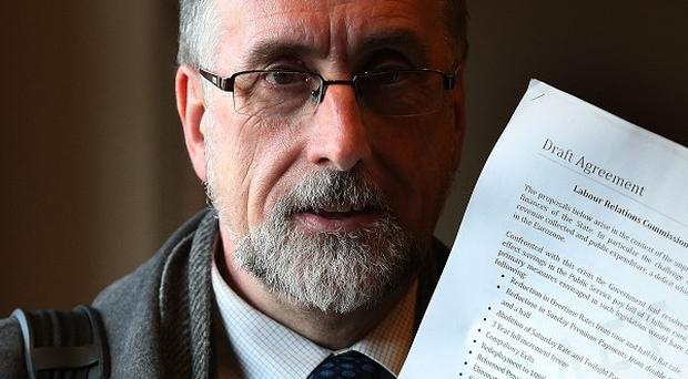 Irish Congress of Trade Unions public services committee chairman Shay Cody holds a draft copy of the agreement