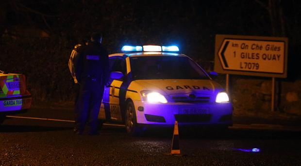 Gardai near the scene where a body was found in a burned out car at Giles Quay near Dundalk