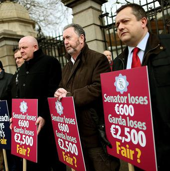 Members of the Garda Representative Association hold placards outside Leinster House