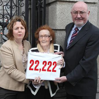 Mairin O'Moore (centre) of the Survivors of Symphysiotomy group presents the petition to Gillian Van Turnout and Caoimhghin O Caolain from the all-party support group at Leinster House, Dublin