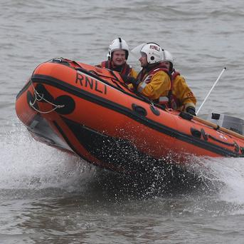 Three people were rescued after a woman and her child were blown out to sea on an inflatable dinghy