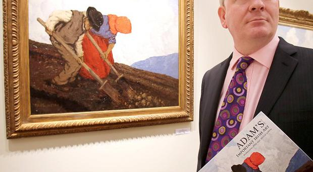 David Britton, director of Adam's, stands next to The Potato Diggers by Paul Henry