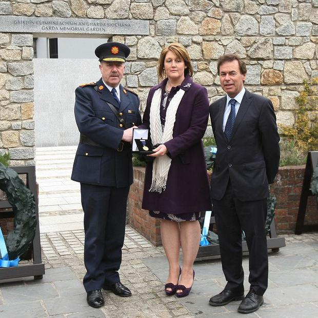 Garda Commissioner Martin Callinan and Justice Minister Alan Shatter present a medal to Adrian Donohoe's wife Caroline