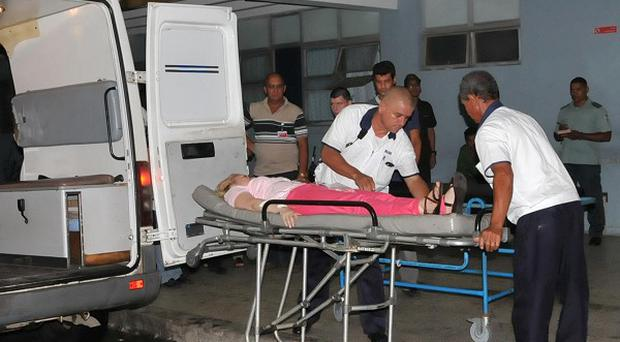 Ambulance workers care for a woman injured in a bus crash in Cuba (AP/Periodico 5 de Septiembre, Juan Carlos Dorado)