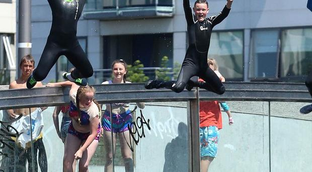 Young people jump into Grand Canal Dock at Dublin city centre