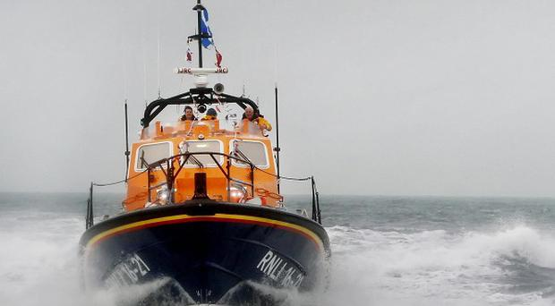 One of the three was airlifted off the lifeboat by the Coast Guard and taken to hospital to be treated for suspected hypothermia
