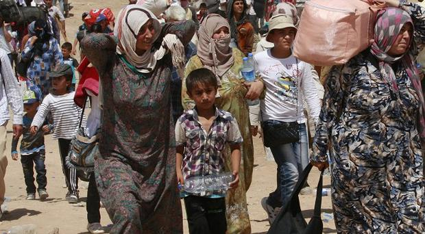 Syrian refugees cross into Iraq at the Peshkhabour border point in Dahuk, 260 miles north-west of Baghdad, Iraq (AP)