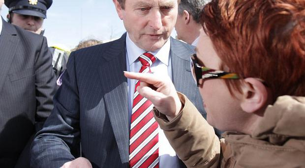 Taoiseach Enda Kenny speaks to former Priory Hall resident Stephanie Meehan at a public event in Baldoyle, Dublin, in May last year
