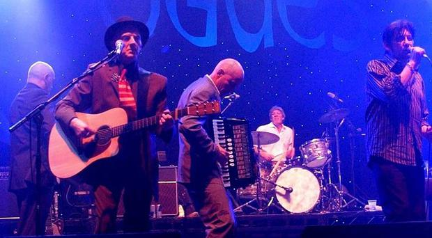Phil Chevron, front left wearing hat, on stage with The Pogues in December 2005