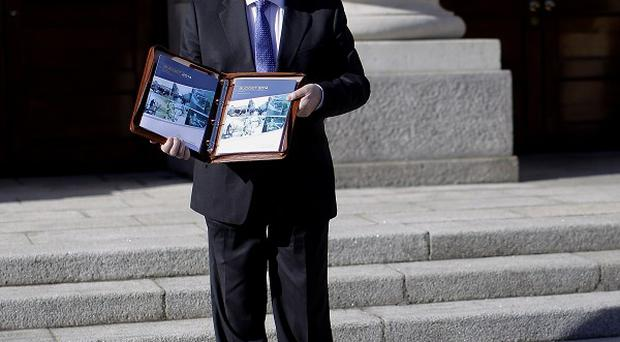 Minister for Finance Michael Noonan poses with the Budget 2014