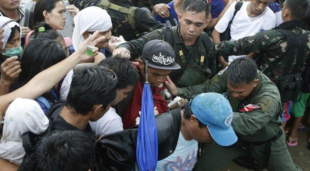 Typhoon survivors in the Philippines jostle to get to emergency supplies (AP)