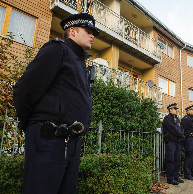 Police officers stand outside flats in Brixton, south London, in the area where three women were allegedly held as slaves for at least 30 years were rescued