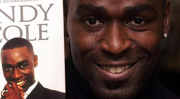 Former Manchester United footballer Andy Cole holding a copy of his autobiography.