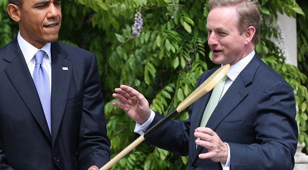 US President Barack Obama holds a hurley presented to him by Taoiseach Enda Kenny