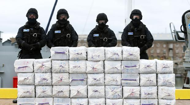 Members of the Irish navy standing behind what is believed to be around a tonne of cocaine seized from the yacht Makayabella.