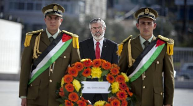 Gerry Adams with Palestinian honor guards lays a wreath at the grave of late Palestinian leader Yasser Arafat in the West Bank city of Ramallah (AP)