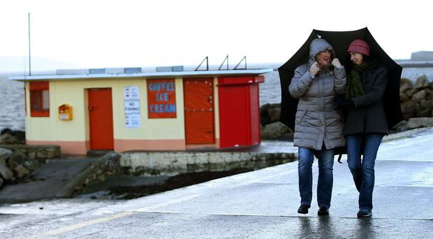 People walk the Salthill promenade, Galway, as Met Eireann issued a weather warning