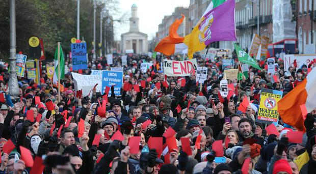 Crowds show red cards to the Government during the Right2Water anti-water charges protest outside Leinster House in Dublin