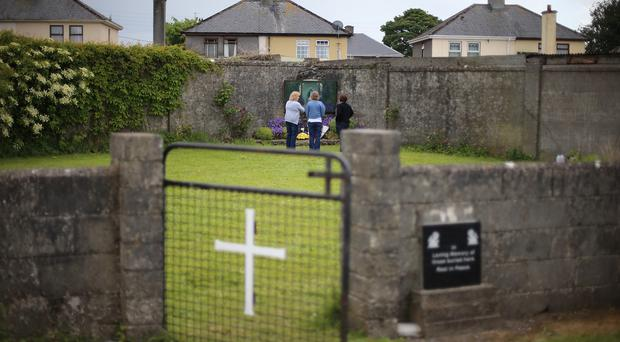 Members of the public at the site of a mass grave for children who died in the Tuam mother and baby home, Galway