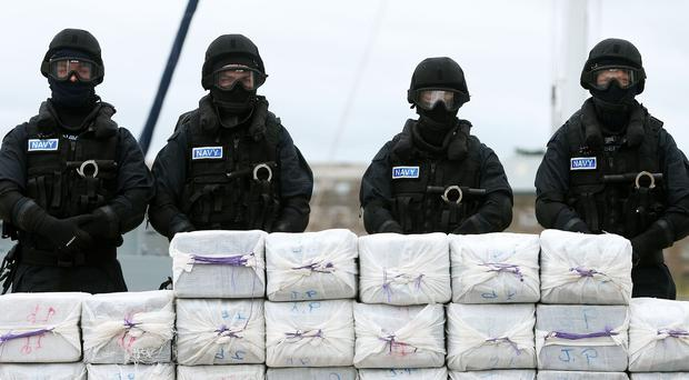 Members of the navy stand behind what is believed to be cocaine which was taken from the yacht Makayabella