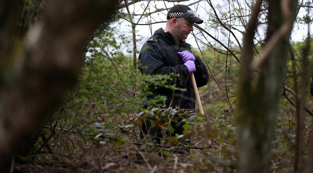 A police officer searches the undergrowth in Dawsholm Park in Glasgow