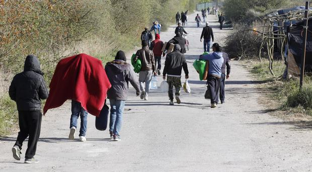 Migrants walk through their makeshift camp near the Jules Ferry centre, outside Calais in northern France (AP)