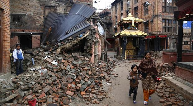 A woman and child walk near the rubble of collapsed buildings at Bhaktapur Durbar Square on the outskirts of Kathmandu, Nepal (AP)