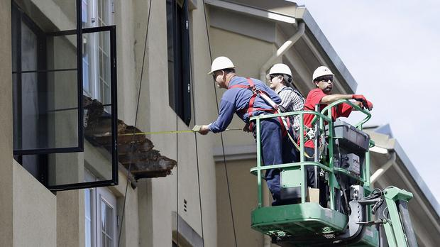 A worker measures near the remaining wood from an apartment building balcony that collapsed in Berkeley (AP)