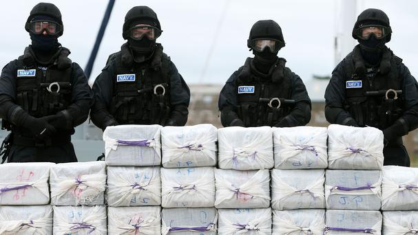 Members of the navy standing behind cocaine which was taken from the yacht Makayabella