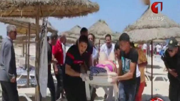 In this screengrab taken from video provided by Tunisia TV1, injured people are treated on a Tunisian beach (Tunisia TV1 via AP)