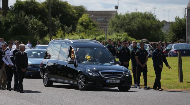 The coffin of Lorna Carty is escorted by players from Meath GAA and Dunderry GAA