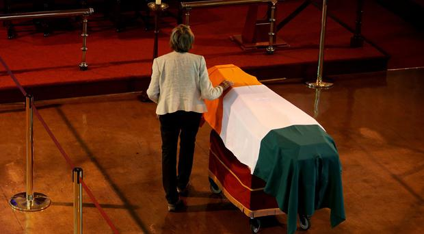 A relative touches the coffin carrying the remains of prominent republican Thomas Kent in St Michael's Garrison Church, Collins Barracks, Cork