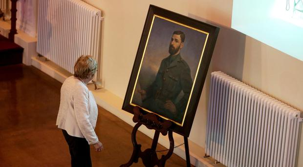 A relative passes a portrait of 1916 Rising leader Thomas Kent