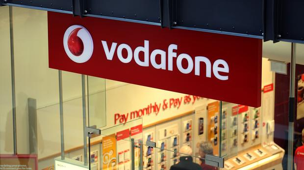Mobile phone giant Vodafone has upped its full-year outlook after growing first half earnings and sales.