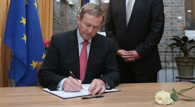 Enda Kenny signs the book of condolence for the victims of the attacks in Paris at the French embassy in Dublin