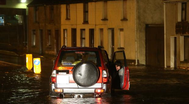 People make their way though floods in the Castlefin area of Donegal