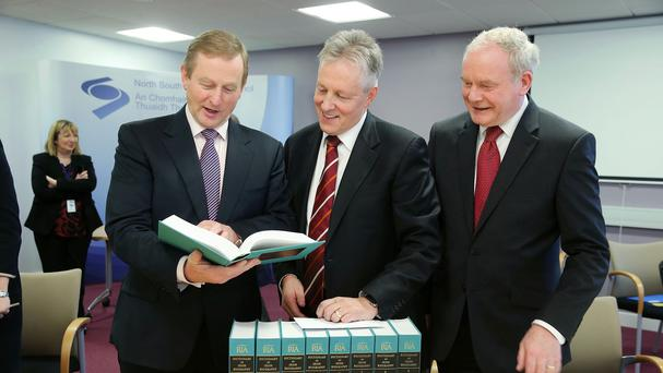 Taoiseach Enda Kenny presents Peter Robinson with nine volumes of the Dictionary of Irish Biography as Martin McGuinness looks on