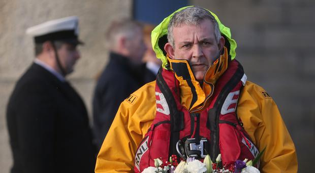 Edward Totterdell, a crew member from Dun Laoghaire RNLI Lifeboat Station, holds a wreath during the ceremony
