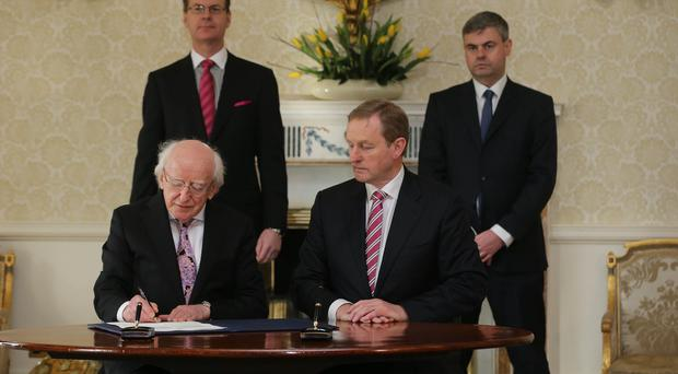 President Michael D Higgins, sitting next to Taoiseach Enda Kenny, sign an order dissolving the Irish parliament and starting the 2016 general election campaign at Aras an Uachtarain in Dublin